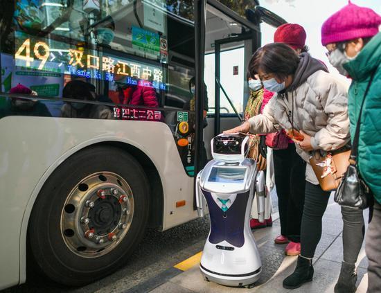 在公交49路人民广场站,一台身着工作服、佩戴口罩的智能机器人吸引了不少乘客关注的目光。受访者供图
