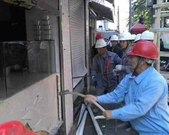 图说:城管正在拆除违法建筑。