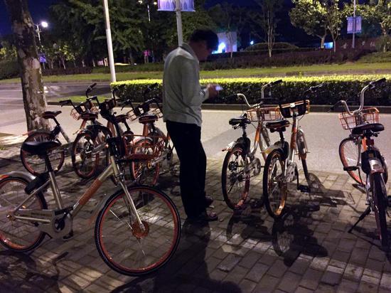 """△已经骑着一辆单车的中年男子,正在寻找另一辆""""红包车""""。"""