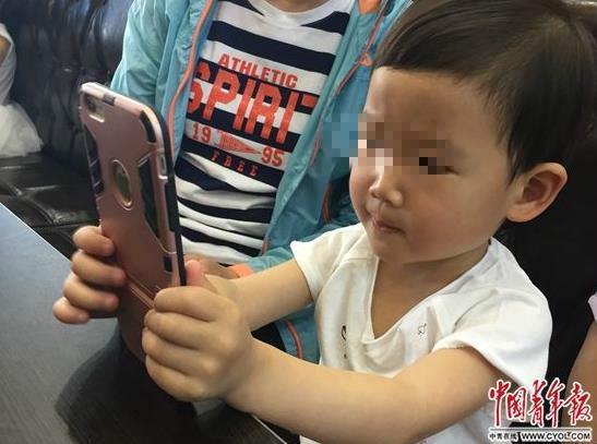 图说:5月14日,天津一家餐厅,一名3岁儿童在等餐期间,用家长的手机聚精会神玩儿游戏。 据中青网