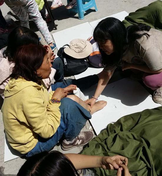 秦艳丽(右)在林场为其他伤员查看伤情。