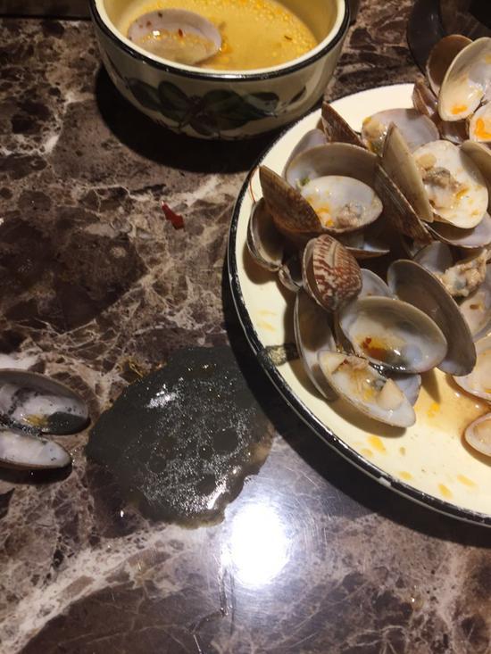 徐小姐回忆,在这家店吃到的部分花蛤里,看到有黑色的煤渣样物体。