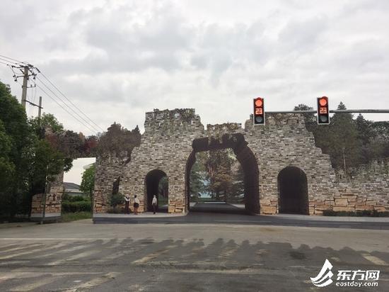 """图片说明:路口这幅逼真的图像,远看似乎真的像立了座""""城门洞""""。"""