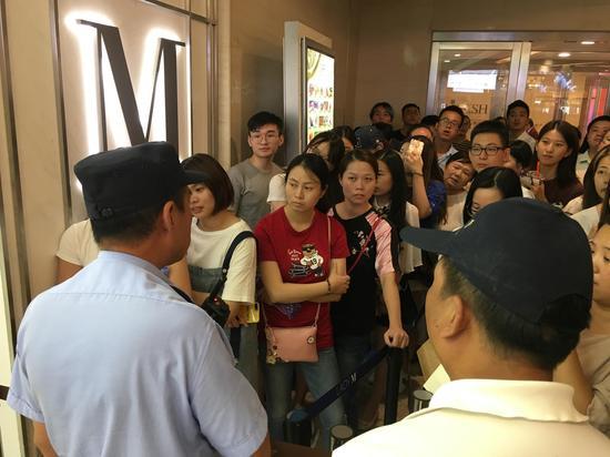 图片说明:民警正在告知排队的人暂停营业的消息。