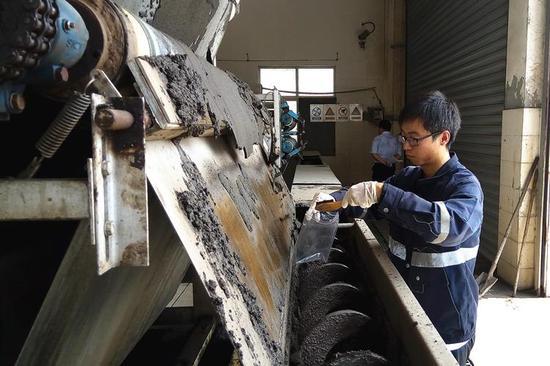 环境监测人员正在铲取污泥,送专业机构检测其中的重金属含量等指标