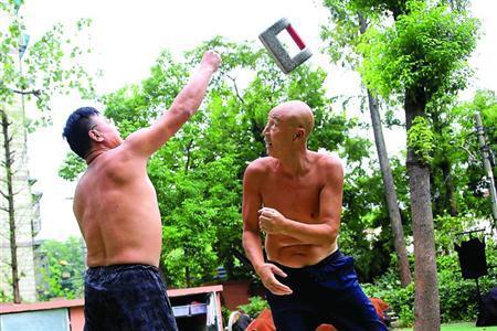 周为民(左)和姜志顺练习双人花锁,两人相距一米左右站定,然后一人将石锁抛出,一人稳稳地用肩、肘或者干脆背过身去接住,配合默契,简直像一个人在抛接一样。