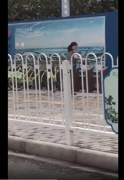 图说:女子持一硬物砸公共自行车固定桩的面板 微博视频供图