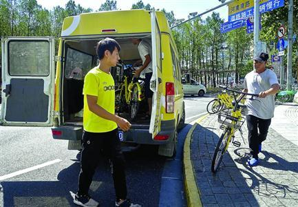 单车企业将联谊大厦门前违停的单车运走 /晨报记者 竺钢