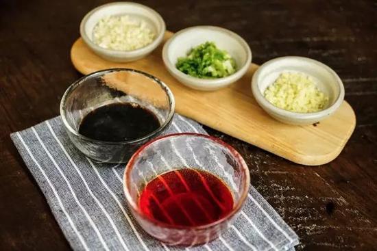 6、鸡腿肉切块铺盘,浇上酱汁和红油,撒葱姜蒜末、花生碎和红辣椒,口水鸡完成。