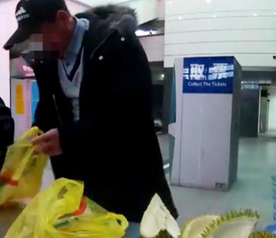图说:男子在安检工作台将榴莲吃完 来源/记录仪拍摄