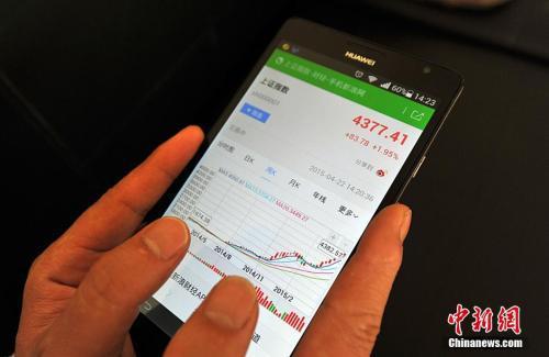 资料图:股民在用手机炒股。 张斌 摄