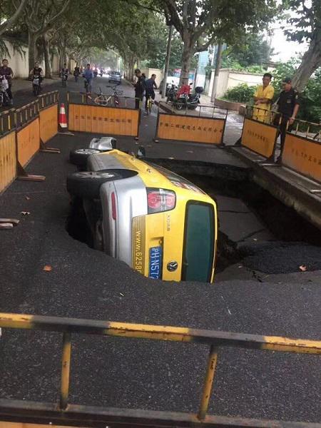 图说:云岭西路一处路面塌陷,途经此处的一辆强生出租车掉入坑中 网友供图