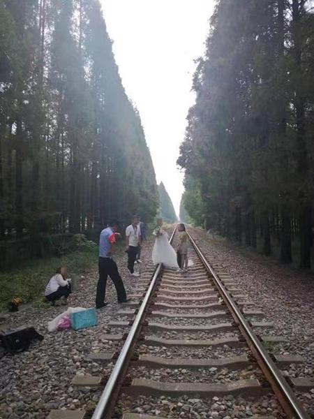 图说:民警制止新人在铁路上摄影。张波 摄
