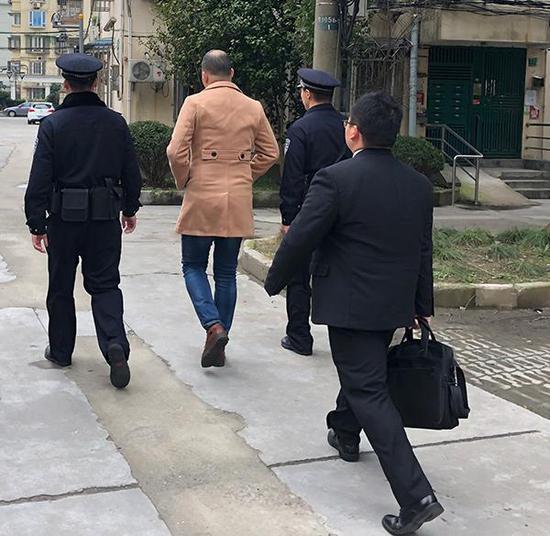 2019年2月27日,被执行人闵军(左二)被法警带回法院。澎湃新闻记者 陈伊萍 摄