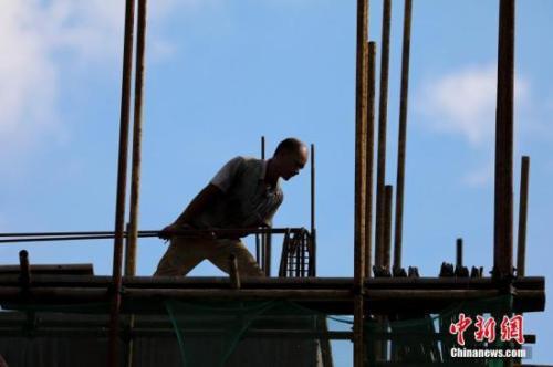 资料图:工人在搬运建筑材料。肖晨威 摄