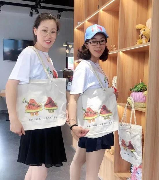 阮林芳(右)与小伙伴一起展示团队设计的文创产品