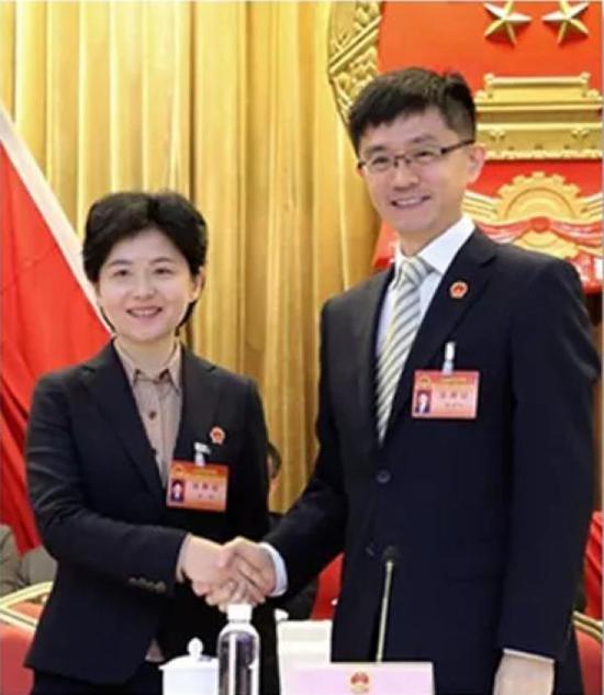 区委书记王为人与王岚握手表示祝贺