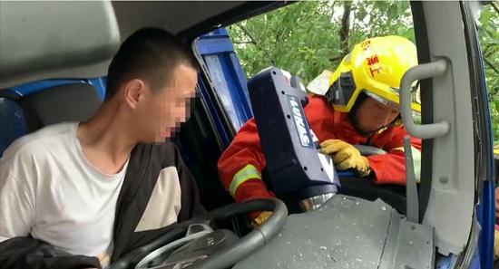 一货车避让行人撞树司机被困 消防到场紧急救援