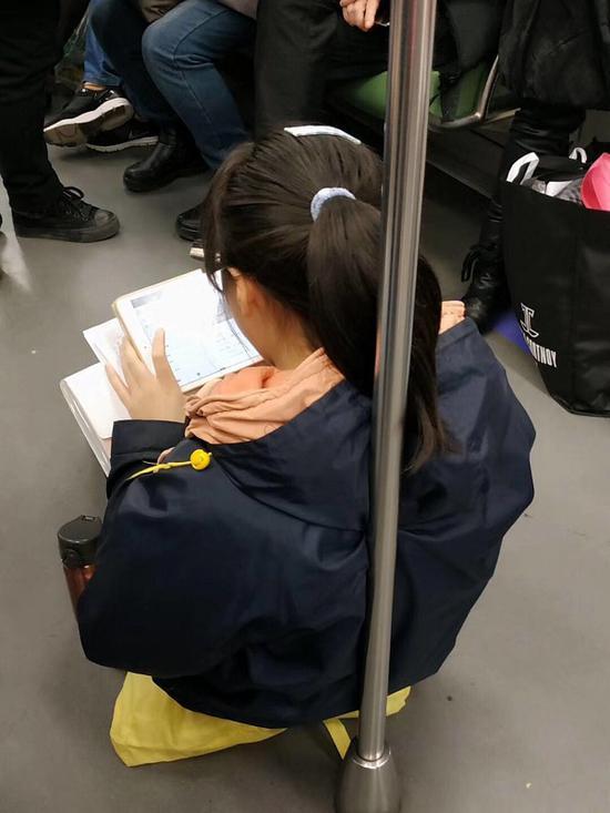 地铁1号线昨日延误 小女孩车厢淡定倚靠扶杆做作业