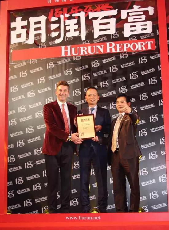 """胡润(左)为罗卡芙家纺董事长吴真生(中)颁发""""产业领袖""""奖。"""