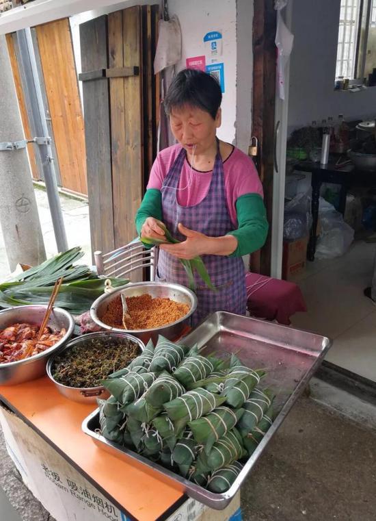 忙着包粽子的康阿姨,从早上5点做到晚上12点,人都瘦了一圈