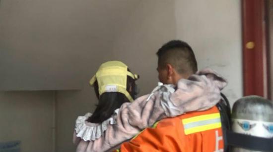 图说:金山一名消防员将防护面罩让给了孕妇并帮助其逃生。金山消防 供图