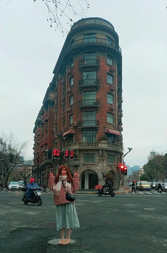 图说:市民站在马路当中,摆着各种造型同武康大楼合影,全然不顾安全