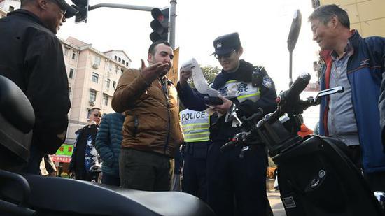 图说:浦东交警对行人、非机动车违法行为进行现场纠正,并开据罚单。浦东警方供图