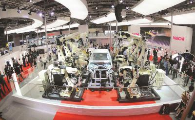 """现场展出的机器人手臂焊接""""无人车间"""",近20台SRA机器人手臂各自分工同时进行汽车焊接作业。本报记者赵立荣摄"""