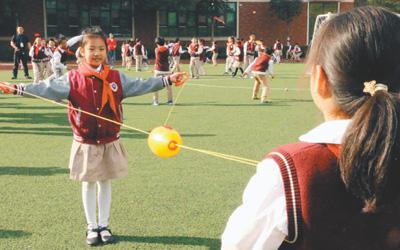 """图说:武汉市红领巾学校学生在操场上分组玩""""穿梭拉拉球""""游戏。"""