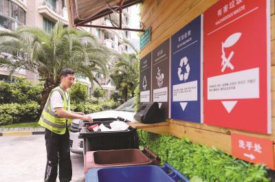 """虹口区嘉兴路街道""""宇泰景苑""""小区,保洁工对居民分类投放的生活垃圾进行分拣。新华社记者方喆摄"""