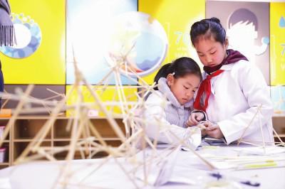 """上海公办中小学""""校园开放日""""如期而至。多所学校打开校门,以丰富多彩的课程和活动,为学生和家长提供了解的平台。图为黄浦区教育学院附属中山学校的学生指导前来参加开放日的学生体验特色课程。本报记者袁婧摄"""
