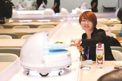 消费者通过送餐机器人取餐。本报记者徐晶卉摄