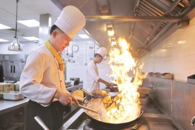黄国平在对年夜饭菜品试菜烹饪。本报记者袁婧摄