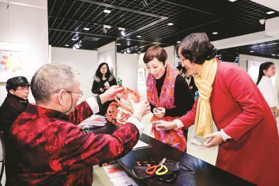蔡氏剪纸技艺传承人蔡德福展示剪纸技艺,与市民一同欢度春节。 (宝山区文广影视局供图)