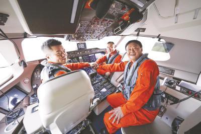 图为钱进(右一)与其试飞机组团队成员。(中国商飞供图)