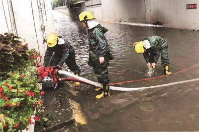 昨天下午在沪闵路莲花南路口隧道内,消防员用抽水泵排水。本报记者赵立荣摄