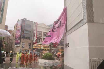 南京东路世茂广场一块巨幅广告被大风吹破,随时有掉落危险,消防人员接报后紧急赶赴现场处置。本报记者叶辰亮摄