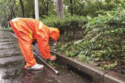 环卫工人冒雨沿街扫树叶,保障下水通畅。本报记者陈龙摄
