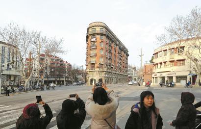 """提升""""颜值""""的武康大楼成市民拍照热门景点。"""