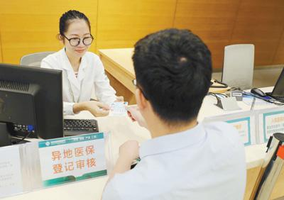 来自天津的王先生在海南省肿瘤医院医保窗口进行异地直接报销结算。   程馨刚摄