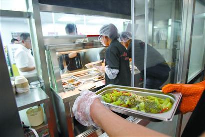 图为菜肴经复热后,放入温水保温柜供顾客挑选。 本报记者 蒋迪雯 摄