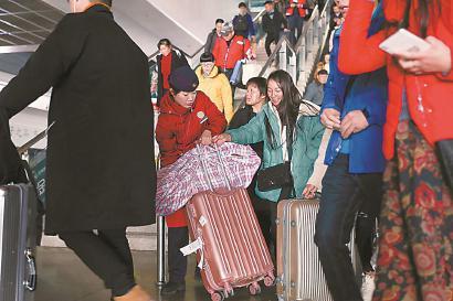 接车员接车员王秋燕帮乘客搬运大件行李。
