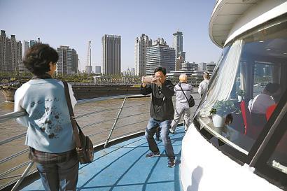 赏景游客在甲板上拍照留念。