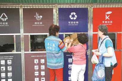居民在垃圾箱房前分类投放垃圾。