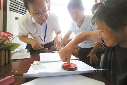 村民在工作人员指导下进行交房签约。本报记者 张海峰 摄