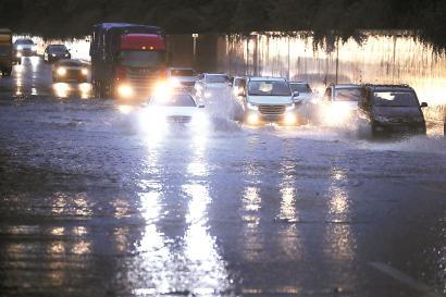 昨天傍晚6时30分,S5外环S20下立交内圈短时积水,车辆缓慢通过。本报记者 张海峰 摄
