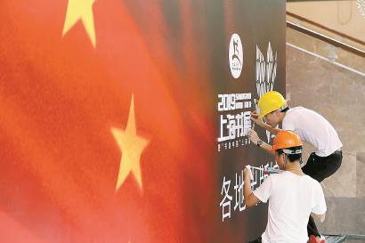 昨天,2019上海书展布展紧锣密鼓,工人站在脚手架上固定招牌。均 本报记者 蒋迪雯 摄