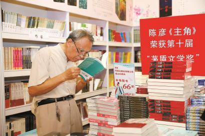 一位老年读者在文学专区精心选购自己心仪的图书。