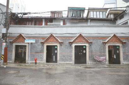 """红砖老建筑灰色尖顶门头上雕着""""梅兰竹菊""""。"""